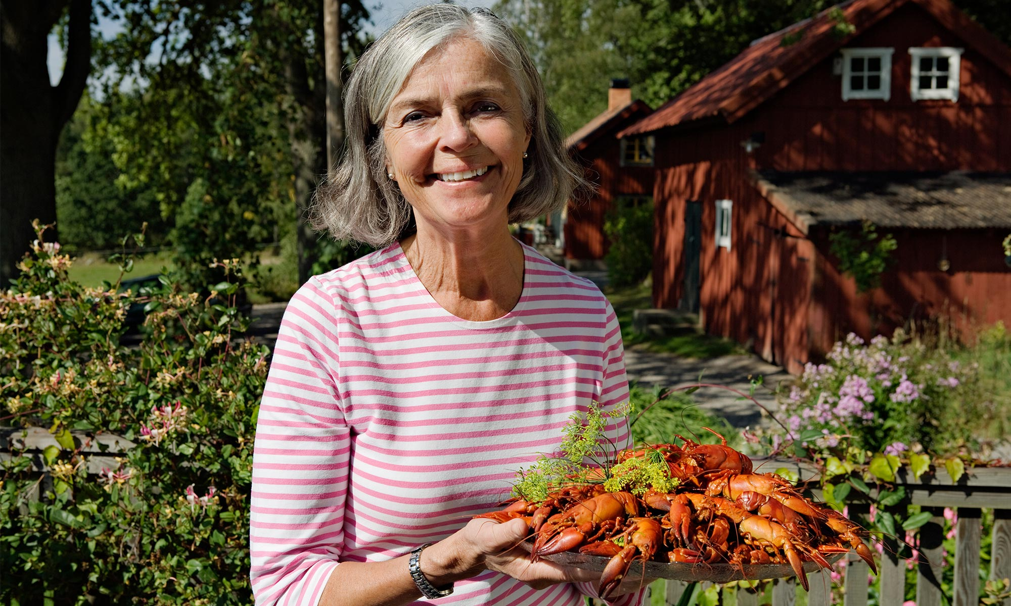 Senior woman holding plate of crayfish in garden.